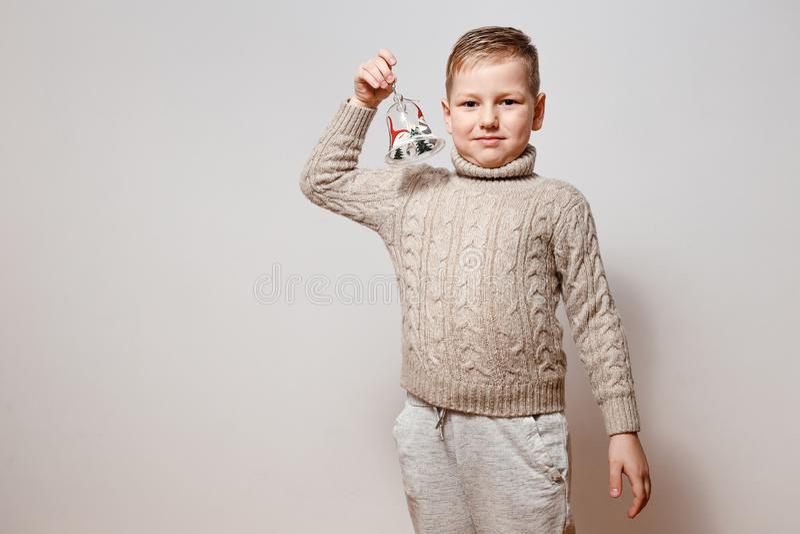 Мальчик в связанном свитере с колоколом в руках стоковое фото