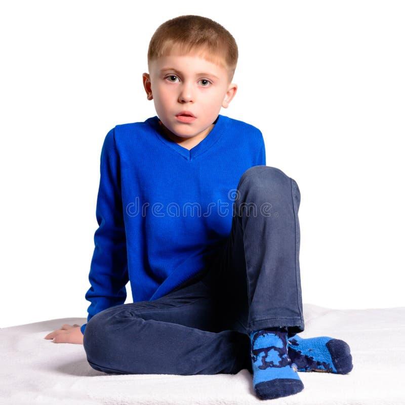 Мальчик в синем пиджаке сидит, изолированный на белой предпосылке стоковое изображение