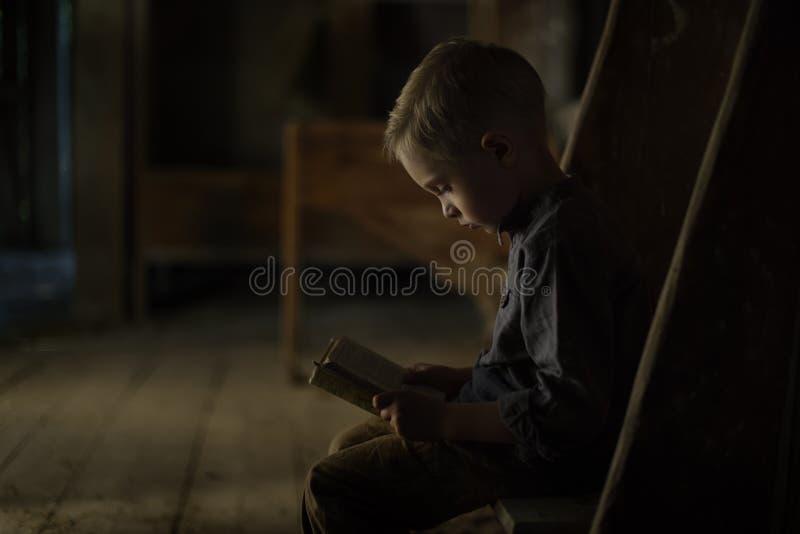 Мальчик в старом доме читая загадочную книгу стоковое фото rf