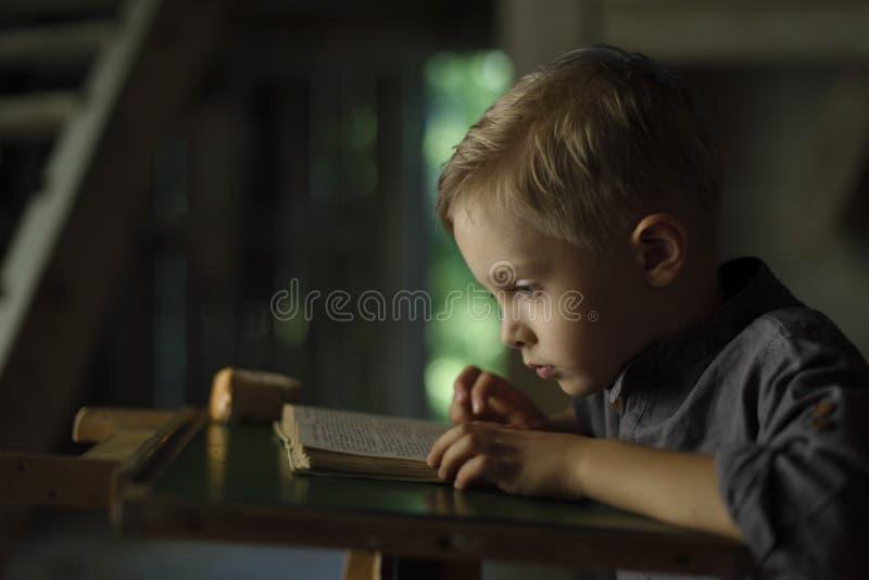 Мальчик в старом доме читая загадочную книгу стоковая фотография rf