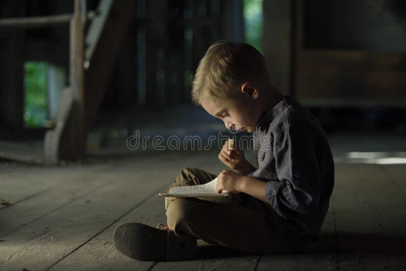 Мальчик в старом доме читая загадочную книгу стоковое фото