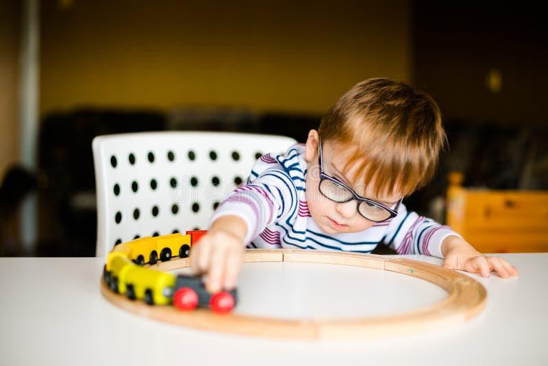 Мальчик в стеклах при рассвет синдрома играя с деревянными железными дорогами стоковое фото