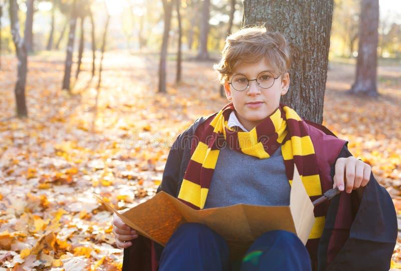 Мальчик в стеклах стоит в парке осени с листовыми золотами, держит книгу в его руках, носит в черной робе стоковые изображения rf