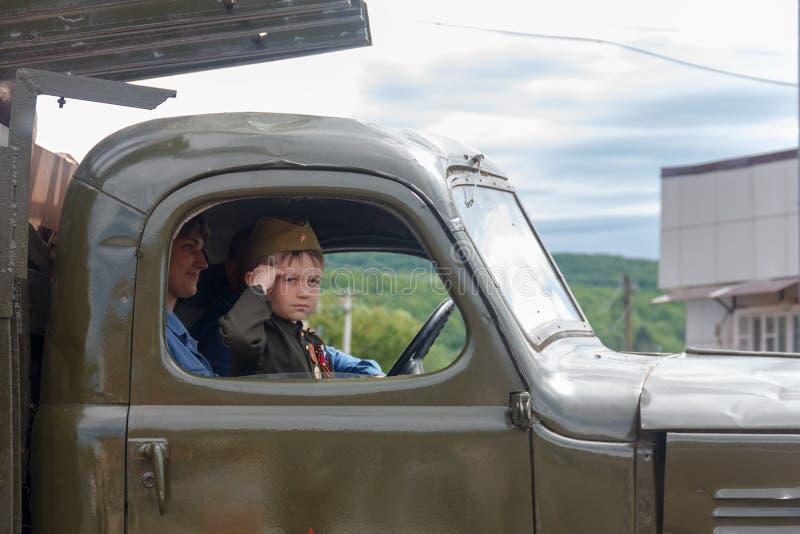 мальчик в форме советского солдата в арене автомобиля армии участвует в параде в честь дня победы стоковое изображение rf