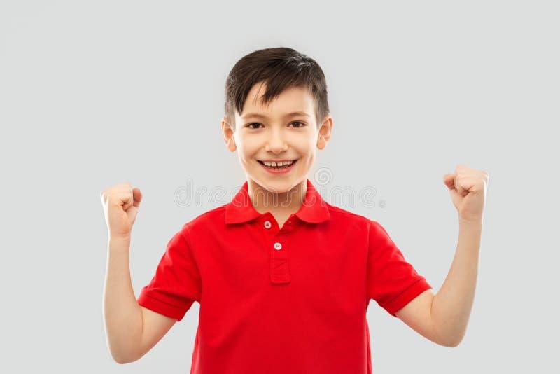 Мальчик в футболке показывая кулаки или выигрывая жест стоковые фотографии rf