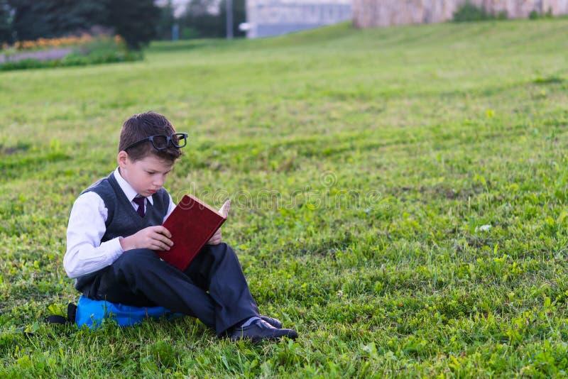 Мальчик в школьной форме сидит на рюкзаке и читает книгу против предпосылки зеленой травы стоковое фото rf