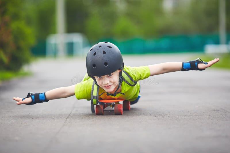 Мальчик в шлеме едет скейтборд стоковые изображения