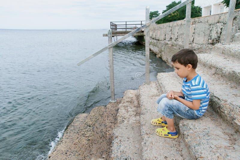 Мальчик в striped футболке на блоке волнореза взморья Мальчик стоя на пляже ребенк стоит на утесе морем стоковая фотография