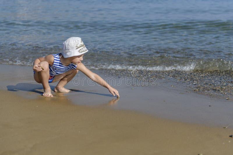 Мальчик в striped футболке на пляже стоковые фотографии rf