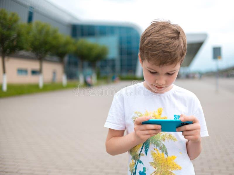 Мальчик говорит по телефону играет игру стоковые фото
