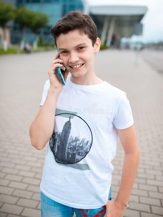 Мальчик говорит по телефону играет игру стоковое фото rf