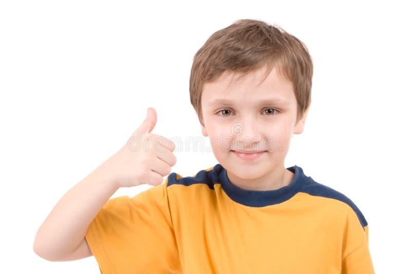 мальчик давая большие пальцы руки поднимает детенышей стоковое фото