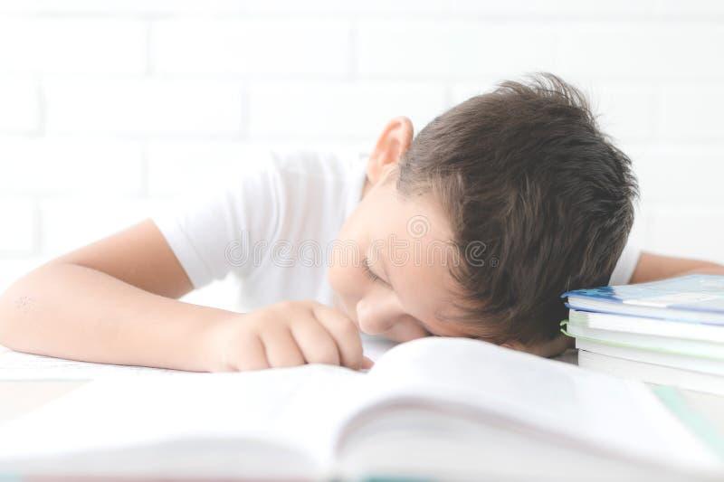 Мальчик делает его домашнюю работу на его столе дома стоковая фотография rf