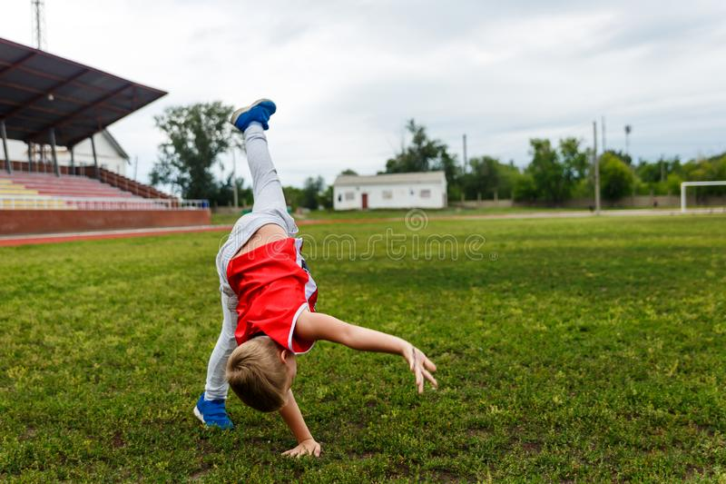 Мальчик делает колесо на траве стоковые изображения rf