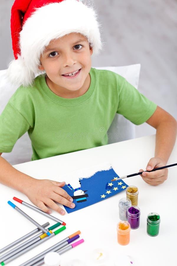 Мальчик делая рождественскую открытку стоковые фотографии rf