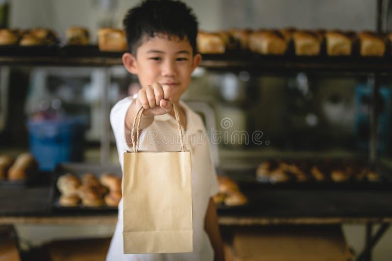 Мальчик держа бумагу сумки стоковые фото