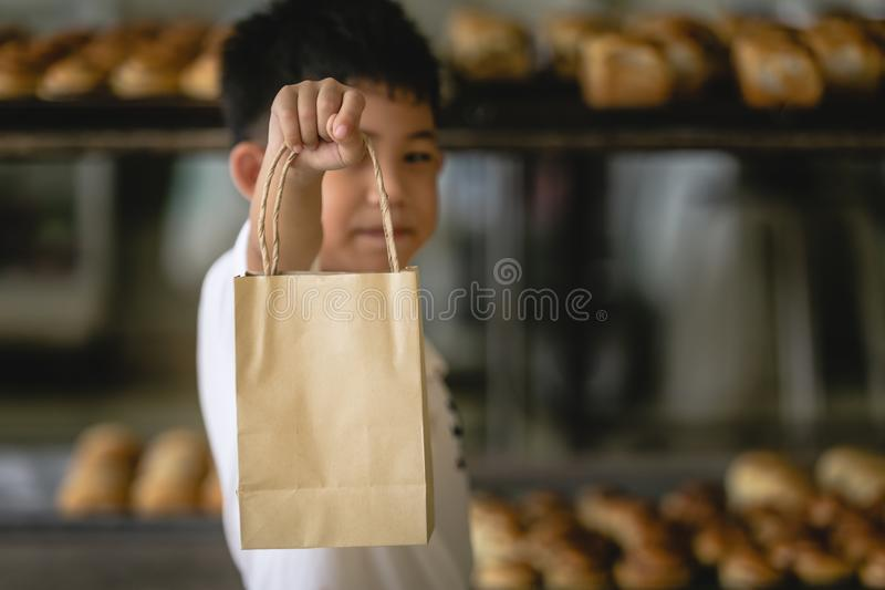 Мальчик держа бумагу сумки стоковое фото