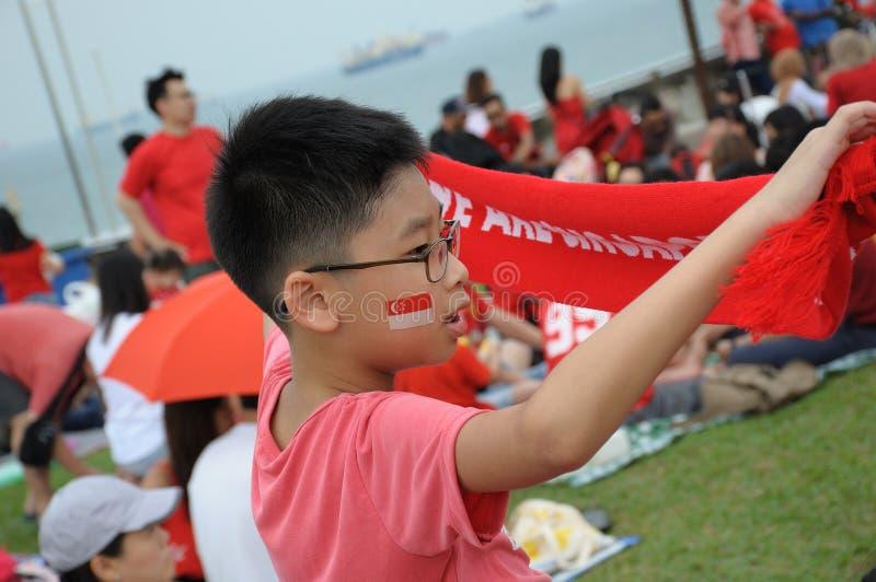 Мальчик держа красное вдохновляющее полотенце во время схода на саде крыши заграждения Марины в Сингапуре стоковая фотография