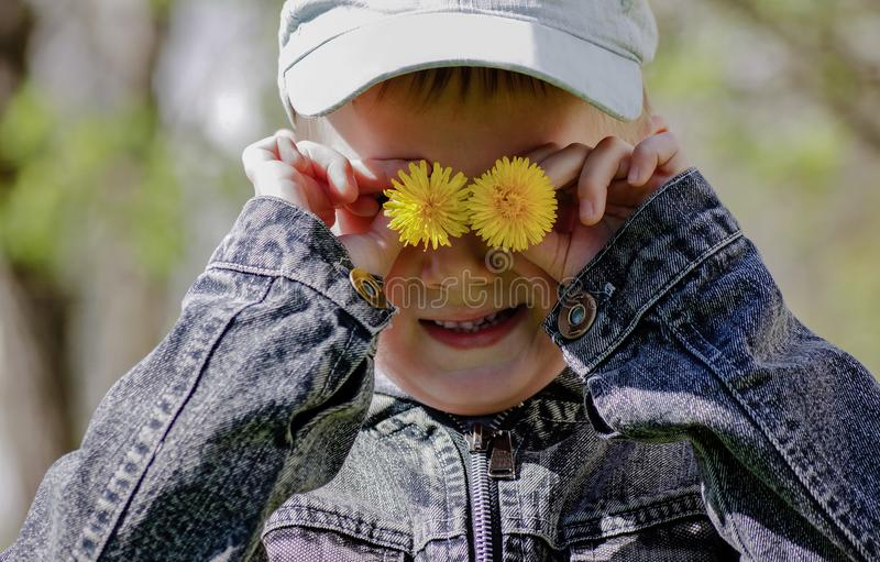 Мальчик держа одуванчики закрывая их глаза стоковое фото