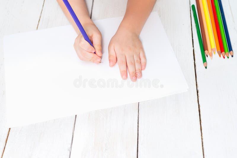 Мальчик держит покрашенный карандаш в его руке и рисует на белизне стоковые фотографии rf