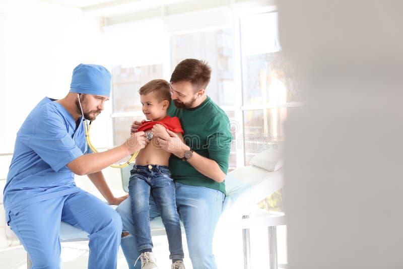 Мальчик доктора детей рассматривая со стетоскопом в больнице стоковые фото