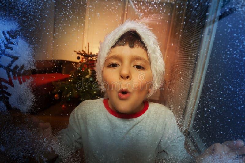Мальчик дуя на морозном окне с снежинкой стоковые фото