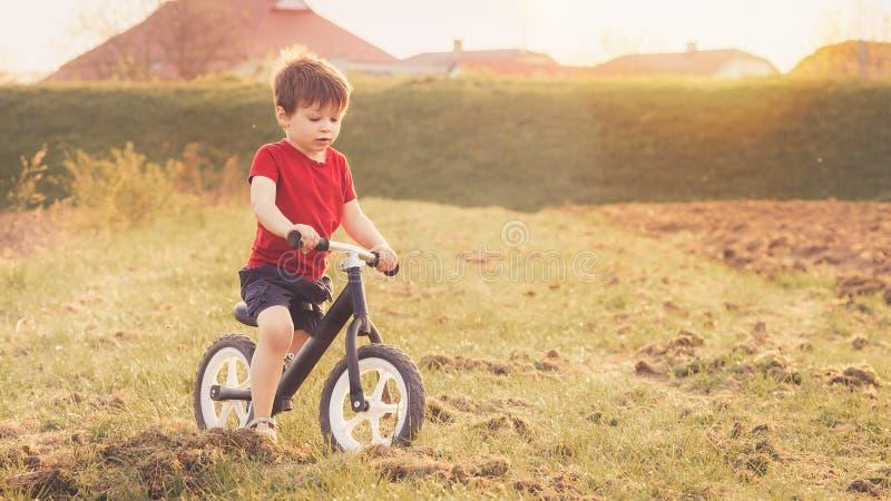 Мальчик едет велосипед баланса в сельской местности стоковое изображение rf