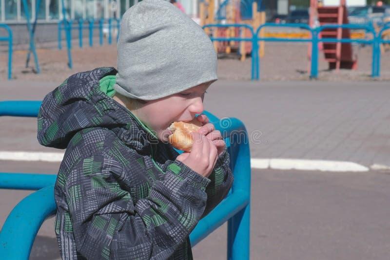Мальчик есть плюшку на спортивной площадке стоковая фотография