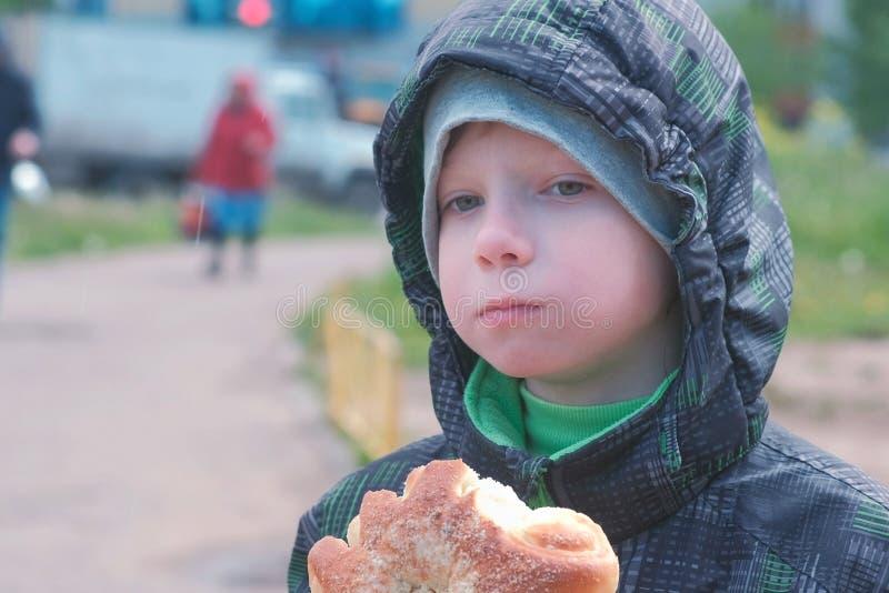 Мальчик есть плюшку на улице стоковые фотографии rf