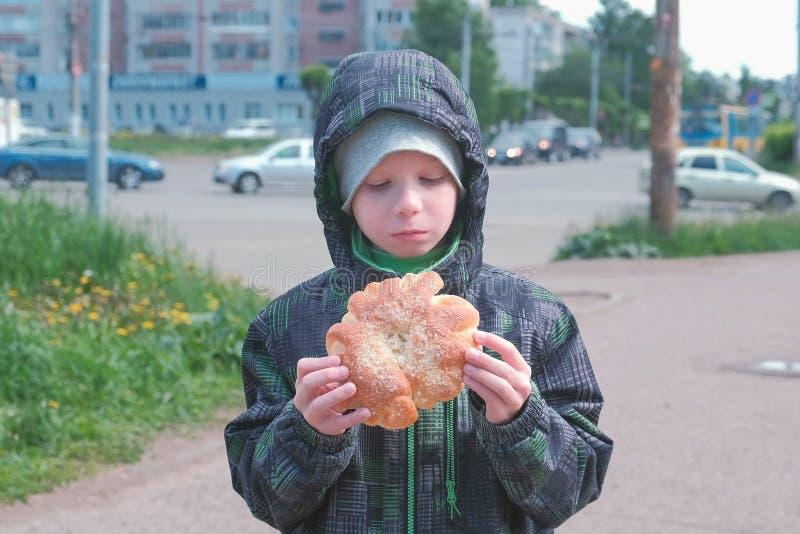 Мальчик есть плюшку на улице стоковые изображения rf