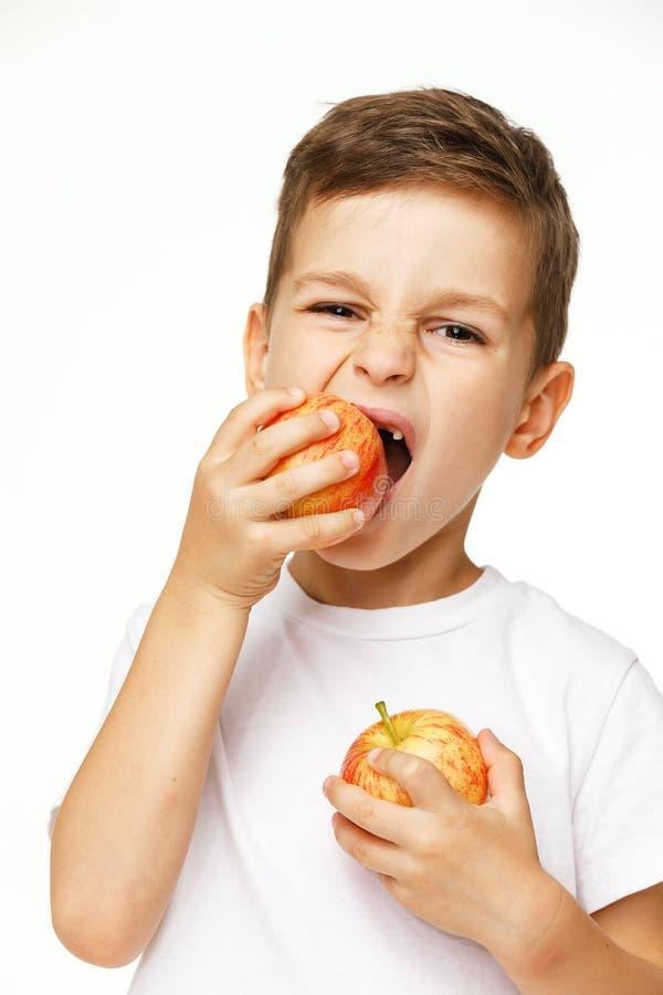 Мальчик ест съемку студии яблока стоковое изображение