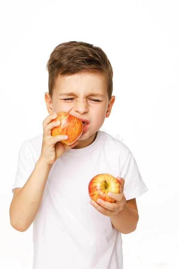 Мальчик ест яблоко с toothache стоковые фотографии rf