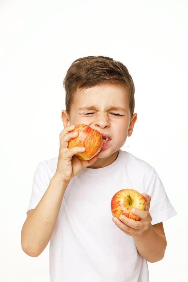 Мальчик ест яблоко с toothache стоковые изображения
