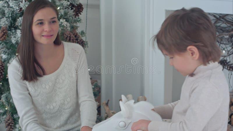 Мальчик ехать деревянная тряся лошадь, пока счастливая мать наблюдая, как он сидел около рождественской елки стоковые фотографии rf