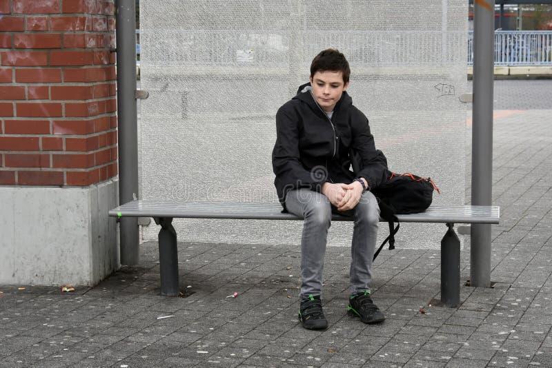 Мальчик ждать на стопе школьного автобуса стоковые фотографии rf