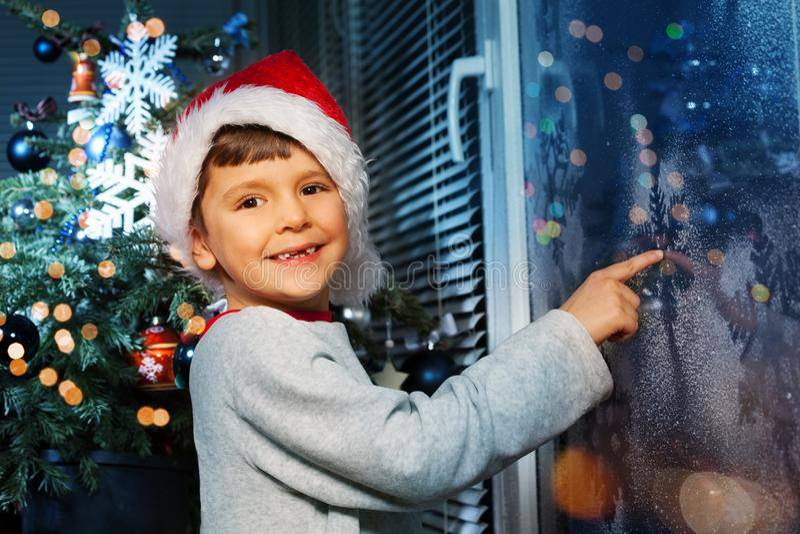 Мальчик ждать Санта около замороженного окна стоковые фотографии rf