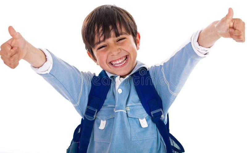 мальчик жизнерадостный его школа показывая большие пальцы руки вверх стоковая фотография rf