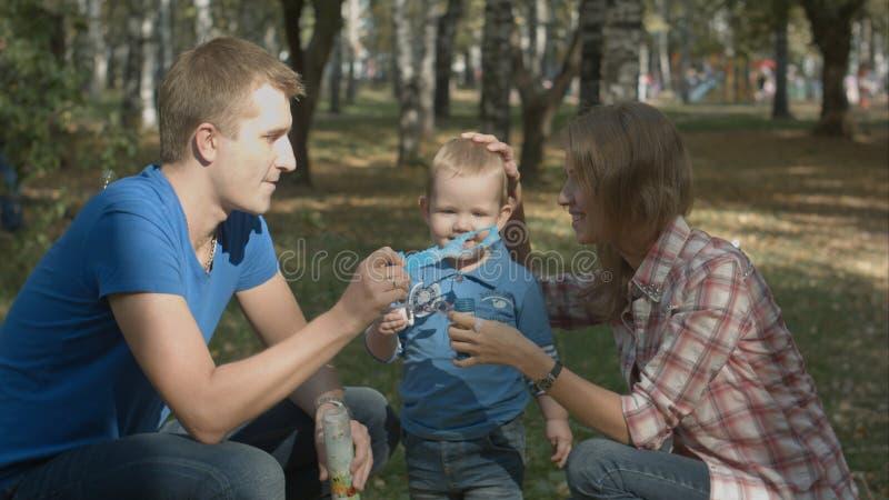 Мальчик играет вместе с его родителями Они играют с мыл-пузырями стоковая фотография rf