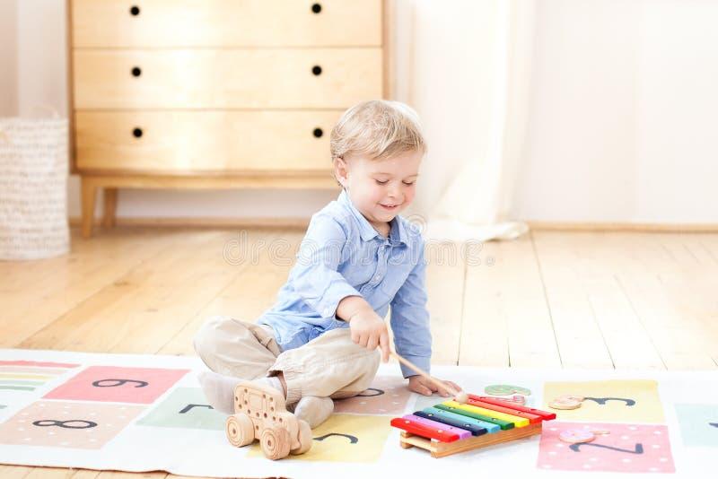 Мальчик играет ксилофон дома Милый усмехаясь положительный мальчик играя с ксилофоном музыкального инструмента игрушки в белизне  стоковые фотографии rf
