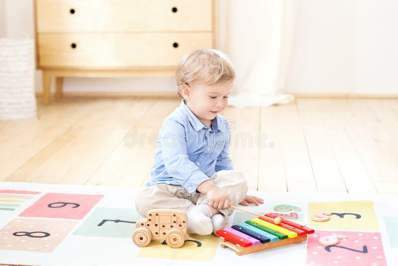Мальчик играет ксилофон дома Милый усмехаясь положительный мальчик играя с ксилофоном музыкального инструмента игрушки в белизне  стоковая фотография rf