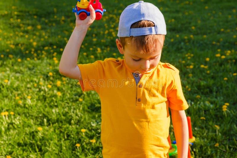 Мальчик играет с автомобилем игрушки на зеленой лужайке стоковая фотография