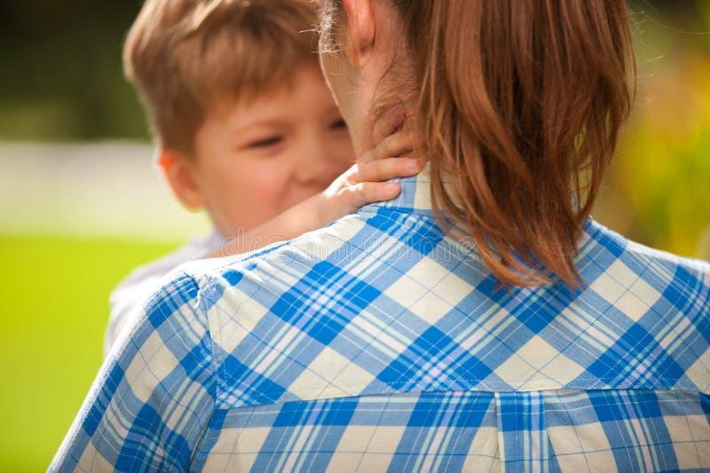 Мальчик играет с его мамой и говорит что-то к ей стоковые изображения