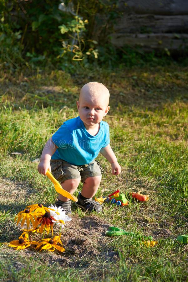 Мальчик играет с игрушками на траве на теплый летний день стоковое фото