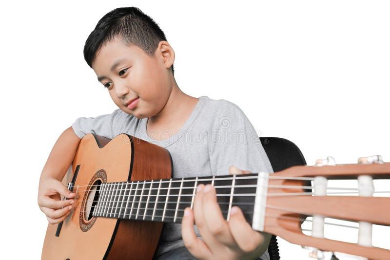 Мальчик играя акустическую гитару стоковое изображение rf