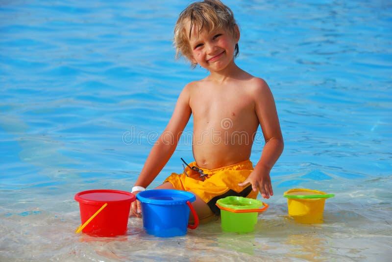 мальчик играя бассеин стоковые фото