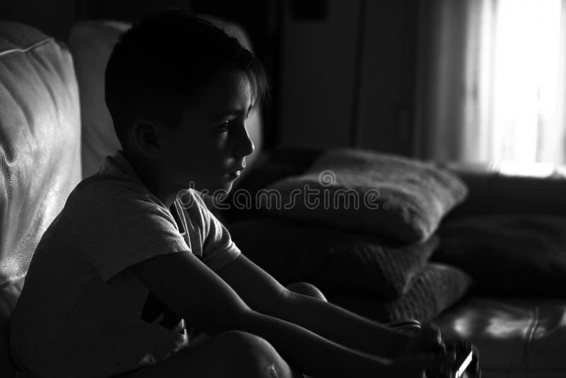 Мальчик играя видеоигры в софе стоковое изображение