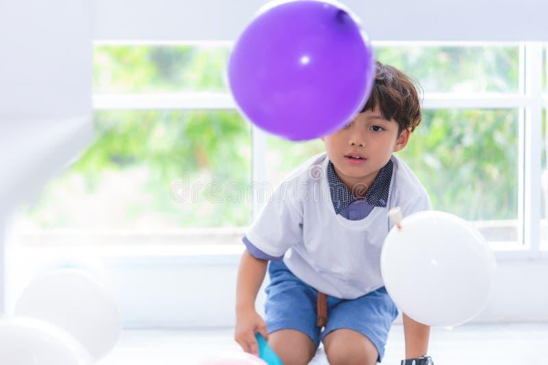 Мальчик играя воздушные шары в вечеринке по случаю дня рождения стоковые фотографии rf