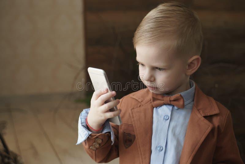 Мальчик играя в игре на телефоне лежа в плюшевом медвежонке белизны игрушки кровати следующем стоковые изображения
