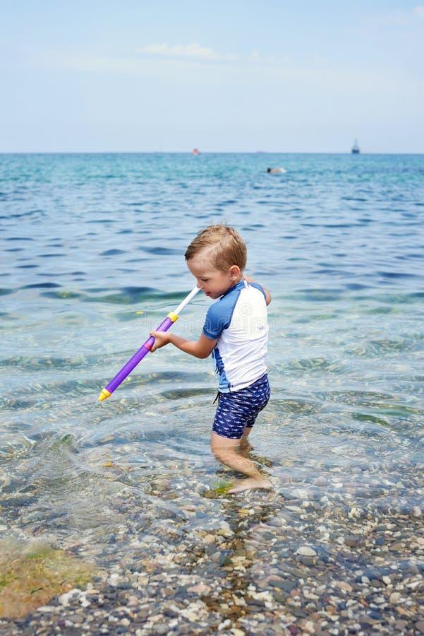 Мальчик играя в море стоковое фото rf