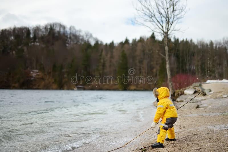 Мальчик играя озером Прогулка ребенка в ветреном и холодном дне стоковые фото